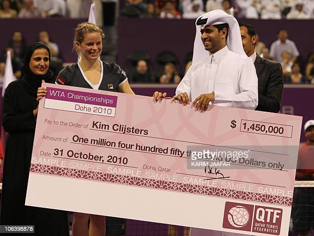 Kim Clijsters of Belgium receives a cheque from Nasser alKhulaifi head of the Qatar Tennis Federation after beating Caroline Wozniacki of Denmark in...