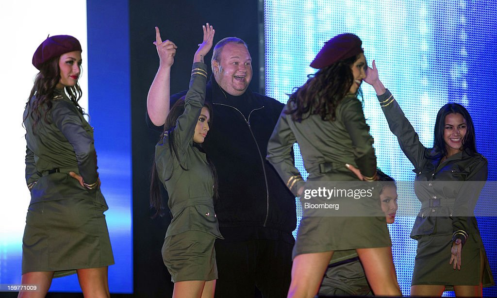 Kim Dotcom, founder of Megaupload.com, gestures while surrounded by dancers during the launch of the company's new website Mega at his mansion in Coatesville, near Auckland, New Zealand, on Sunday, Jan. 20, 2013. Dotcom, marking one year since his Megaupload.com website was shut down by the U.S. Department of Justice and his home raided by New Zealand tactical squad officers in helicopters, unveiled his new website Mega, a successor file-storage and sharing site, saying innovation won't be stopped. Photographer: Brendon O'Hagan/Bloomberg via Getty Images