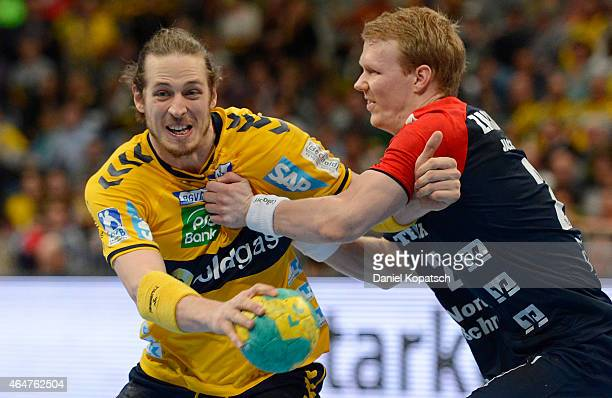 Kim Ekdahl Du Rietz of RheinNeckar Loewen is challenged by Anders Zachariassen of Flensburg during the DKB HBL Bundesliga match between RheinNeckar...