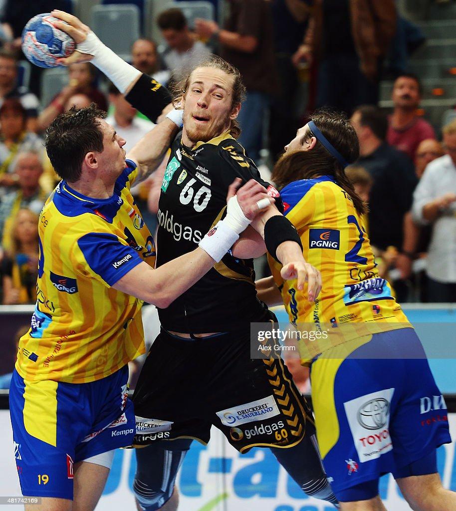 Kim Ekdahl du Rietz of RheinNeckar Loewen is challenged by Krzysztof Lijewski and Ivan Cupic of Kielce during the Velux EHF Champions League Round of...