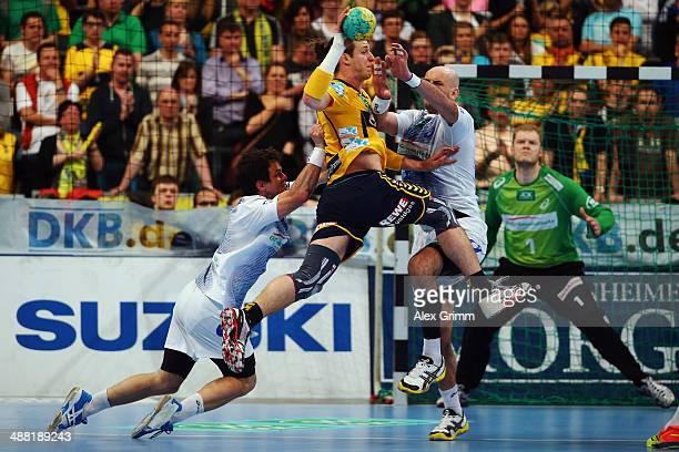 Kim Ekdahl du Rietz of RheinNeckar Loewen is challenged by Matthias Flohr and Davor Dominikovic of Hamburg during the DKB Handball Bundesliga match...