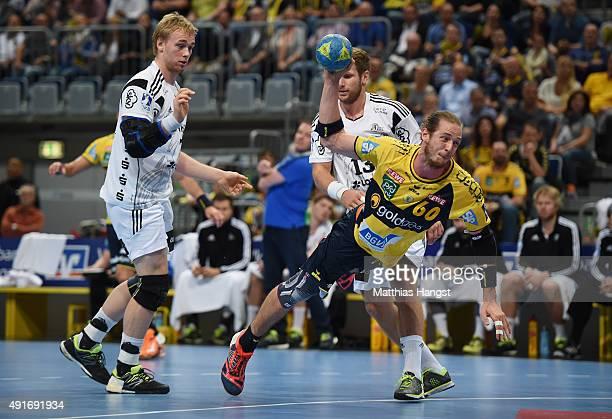 Kim Ekdahl Du Rietz of RheinNeckar Loewen is challenged by Rene Toft Hansen of Kiel and Steffen Weinhold of Kiel during the DKB HBL Bundesliga match...