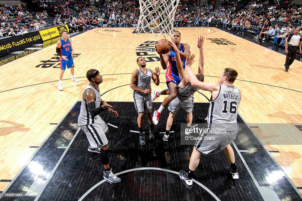 Kim English #24 of the Detroit Pistons attempts a shot in the lane against Nando de Colo #25, Patty Mills #8 and Aron Baynes #16 of the San Antonio Spurs on March 3, 2013 at the AT&T Center in San Antonio, Texas.