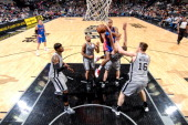 Kim English of the Detroit Pistons attempts a shot in the lane against Nando de Colo Patty Mills and Aron Baynes of the San Antonio Spurs on March 3...