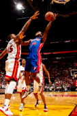 Kim English of the Detroit Pistons shoots against Dexter Pittman of the Miami Heat during a preseason game on October 18 2012 at American Airlines...