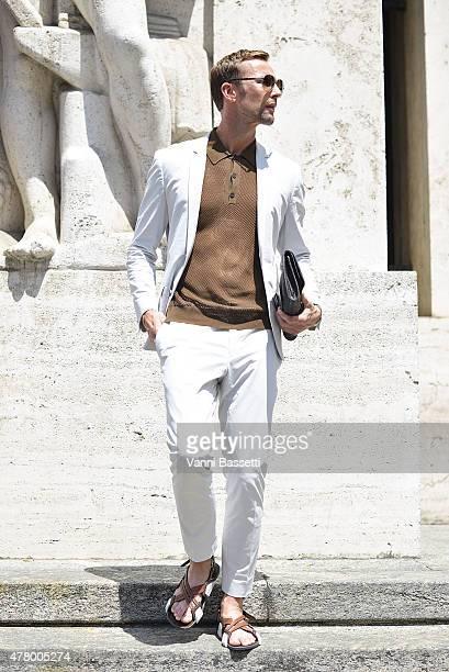 Kim Genaa poses wearing Calvin Klein suit Dries Van Noten polo shirt and Prada sandals on June 21 2015 in Milan Italy