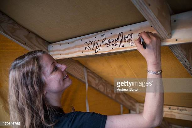 Kim Holleman signs her name on the inside of her bivouac while camping on an undisclosed rooftop on June 15 2013 in the Brooklyn Borough of New York...