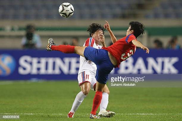 Kim Hyeri of South Korea shoots past Ri Regyong of North Korea during the WomenÕs Football Semifinal Match on day ten of the 2014 Asian Games at...