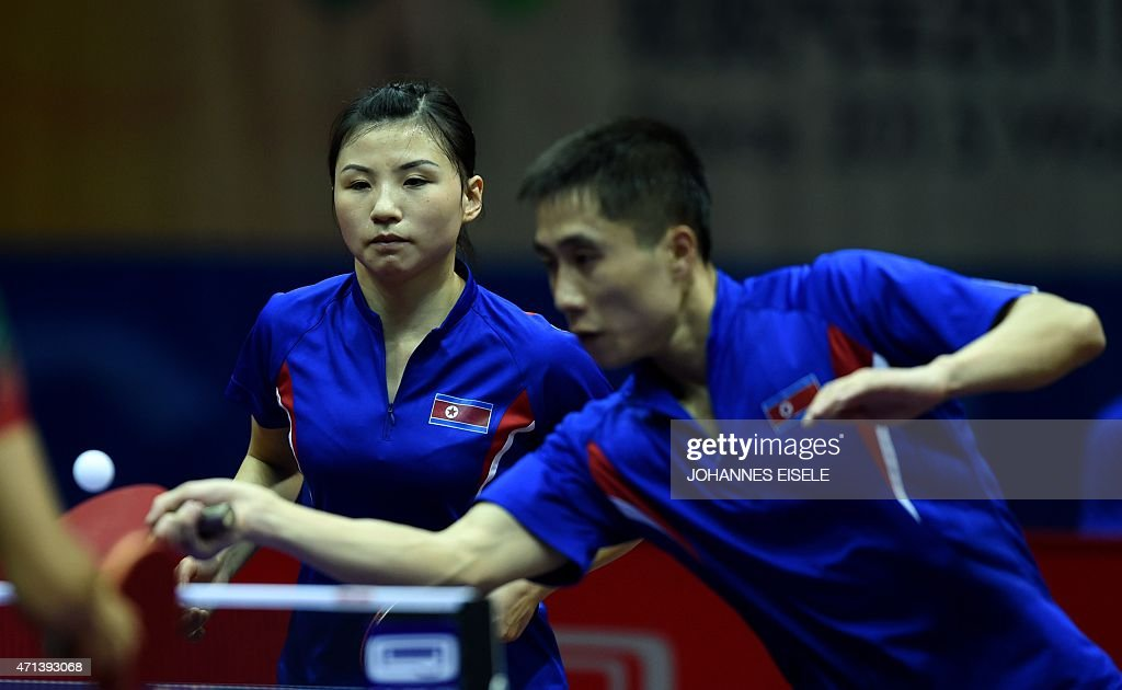 Kim Hyok Bong and <a gi-track='captionPersonalityLinkClicked' href=/galleries/search?phrase=Kim+Jong+-+Table+Tennis+Player&family=editorial&specificpeople=5499597 ng-click='$event.stopPropagation()'>Kim Jong</a> of South Korea serve a ball during their mixed doubles match against Diogo Chen and Leila Oliveira of Portugal in the 2015 World Table Tennis Championships at the Suzhou International Expo Center in Suzhou, Jiangsu province on April 28, 2015.
