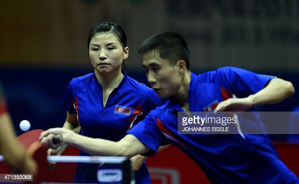 Kim Hyok Bong and Kim Jong of South Korea serve a ball during their mixed doubles match against Diogo Chen and Leila Oliveira of Portugal in the 2015...