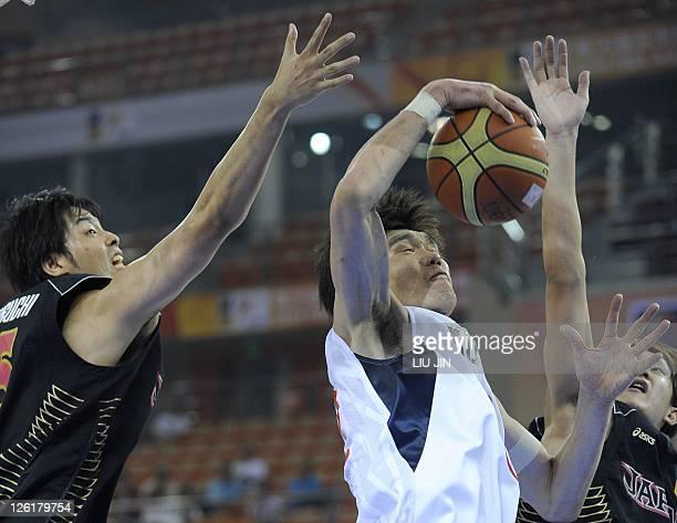 Kim Joo Sung of South Korea controls the ball as Takeuchi Joji and Kawamura Takuya of Japan defend during the quarterfinal match at the 26th Asian...