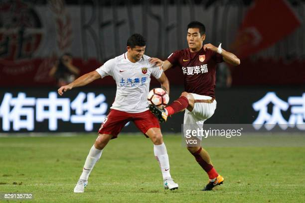Kim Juyoung of Hebei China Fortune and Elkeson of Shanghai SIPG vie for the ball during the 21st round match of 2017 China Super League between Hebei...