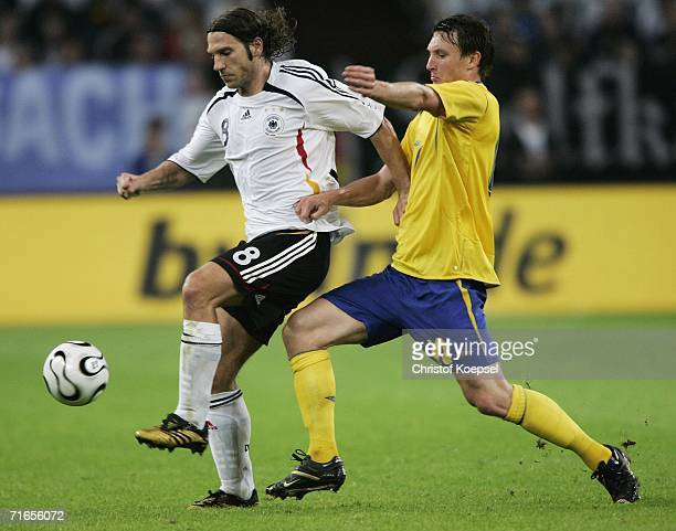 Kim Kallstrom of Sweden tackles Torsten Frings of Germany during the friendly match between Germany and Sweden at the Arena Auf Schalke on August 16...