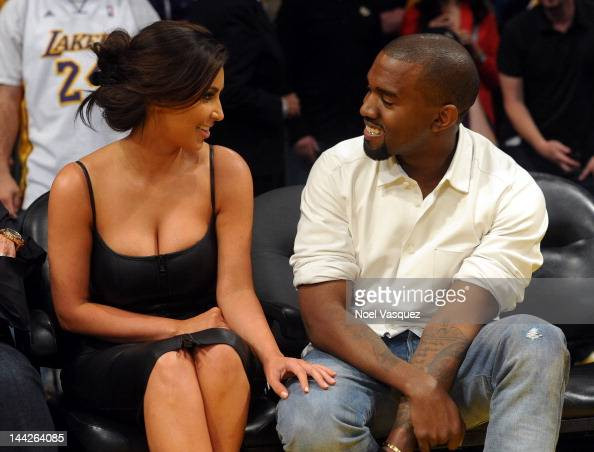Kim Kardashian and Kanye West talk from their courtside seats before the Los Angeles Lakers take on the Denver Nuggets in Game Seven of the Western...