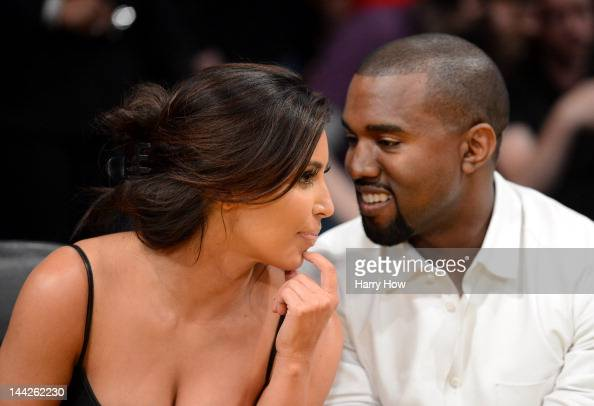 Kim Kardashian and rapper Kanye West talk from their courtside seats before the Los Angeles Lakers take on the Denver Nuggets in Game Seven of the...