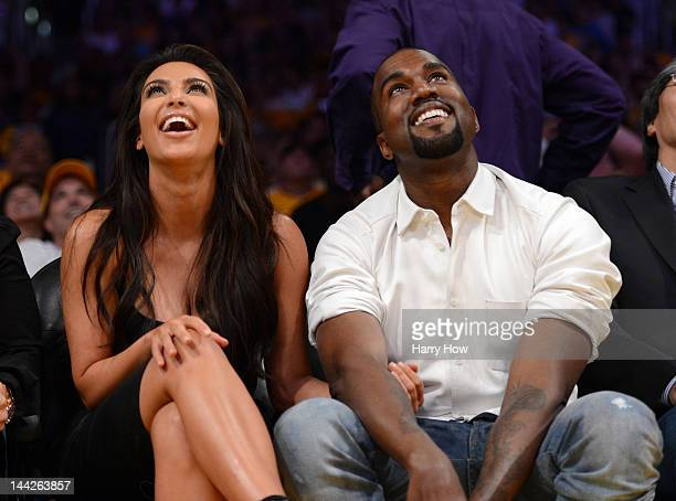 Kim Kardashian and rapper Kanye West watch the video board from their courtside seats as the Los Angeles Lakers take on the Denver Nuggets in Game...