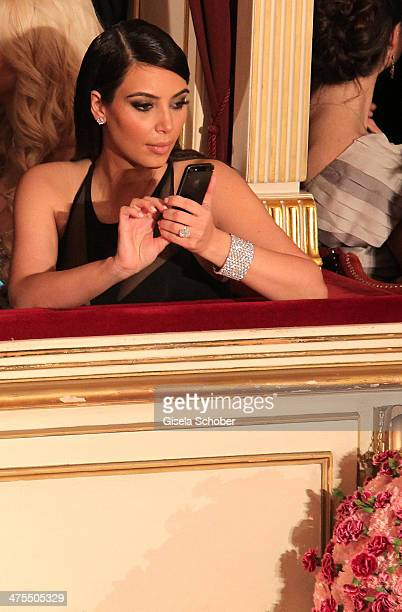 Kim Kardashian holds her mobile phone during the traditional Vienna Opera Ball at Vienna State Opera on February 27 2014 in Vienna Austria