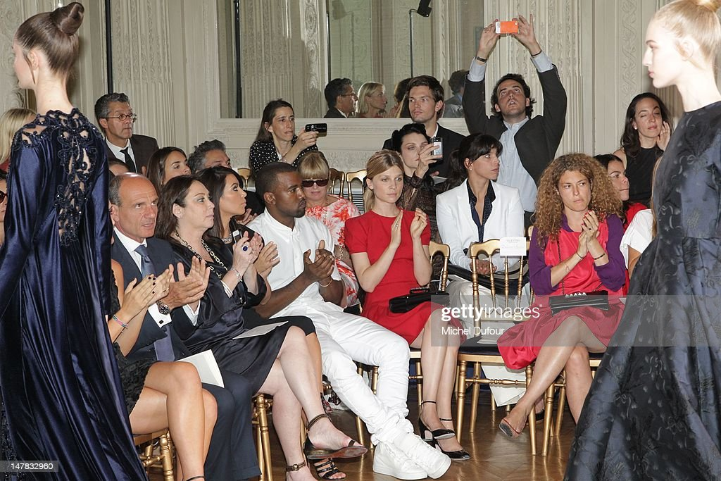 Kim Kardashian, Kanye West and Clemence Poesy observe as a model walks the runway during the Valentino Haute-Couture Show as part of Paris Fashion Week Fall / Winter 2013 at Hotel Salomon de Rothschild on July 4, 2012 in Paris, France.
