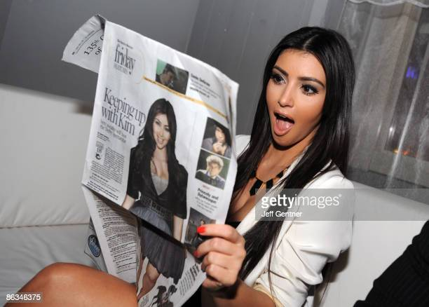 Kim Kardashian reads a Louisville Courier Journal newspaper featuring herself at the 2nd Annual Derby Spectacular celebration at Glassworks on May 1...