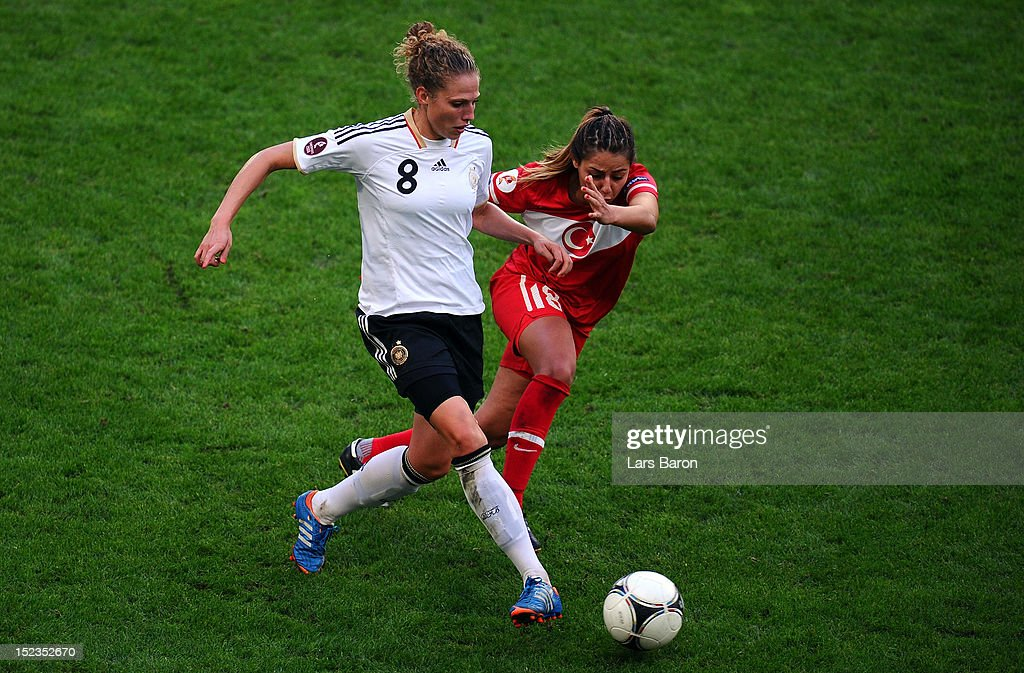 <a gi-track='captionPersonalityLinkClicked' href=/galleries/search?phrase=Kim+Kulig&family=editorial&specificpeople=2194725 ng-click='$event.stopPropagation()'>Kim Kulig</a> of Germany is challenged by Eyluel Elgalp of Turkey during the UEFA Womens Euro 2013 qualification match between Germany and Turkey at Schauinsland-Reisen-Arena on September 19, 2012 in Duisburg, Germany.