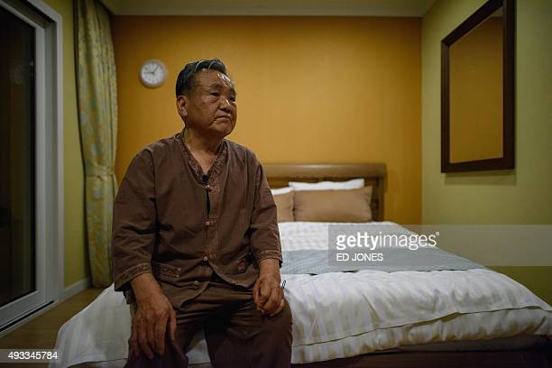 Kim KunHo sits on his bed the night before departing to visit his North Korean brotherinlaw at a family reunion in North Korea at a hotel used as a...