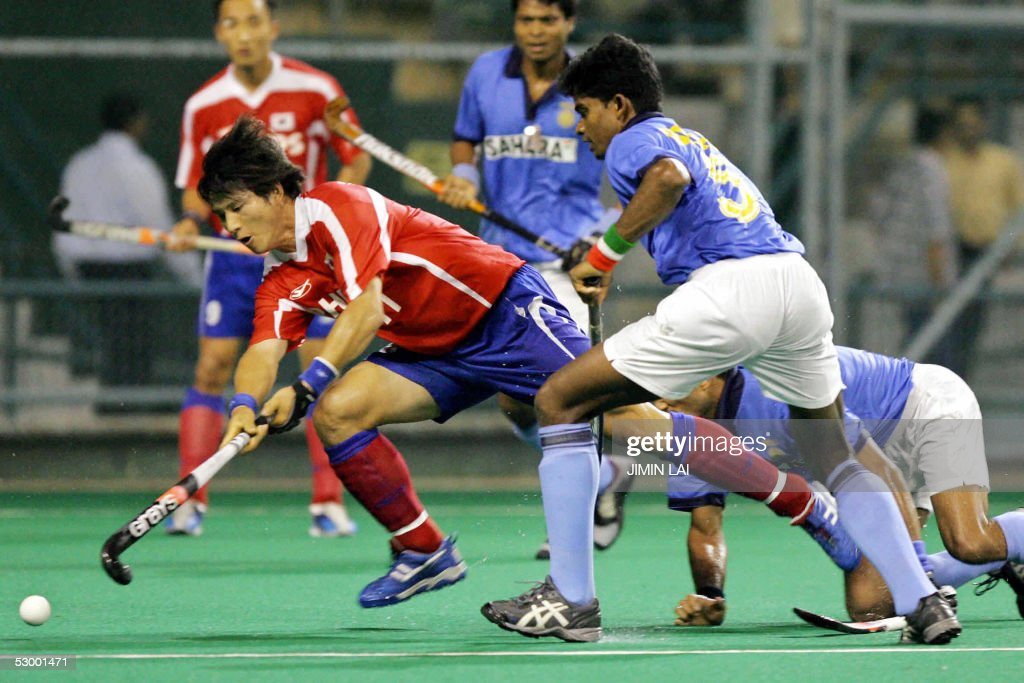 Kim Kyung Seok of Korea gets away with the ball while Bimal Lakra of India looks on during the match between India and Korea at the Sultan Azlan Shah...