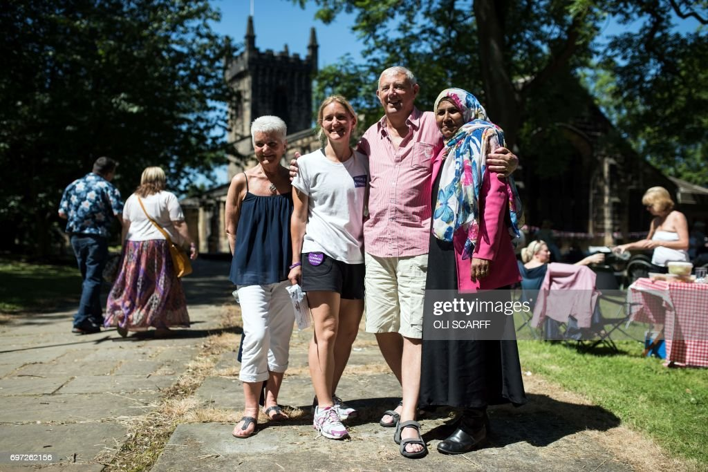 Kim Leadbeater (4L), Jean Leadbeater (3L) and Gordon Leadbeater (5L), the sister, mother and father of murdered Member of Parliament Jo Cox, pose for a photograph with family friend Razia Qadri (R) as they attend a 'Great Get Together' community service and picnic in memory of Jo Cox, marking the first anniversary since her killing, in the grounds of All Saints Church in Batley, northern England on June 18, 2017. The Great Get Together weekend is Inspired by murdered Labour MP Jo Cox's belief that we have more in common than which divides us, a line from her first speech to Parliament, and is a community initiative designed to unite people and communities on the streets and parks of their neighbourhoods. The 41 year-old Labour Party MP, Jo Cox, was assassinated by a pro-Nazi sympathiser in a terror attack in her constituency in northern England on June 16, 2016. /