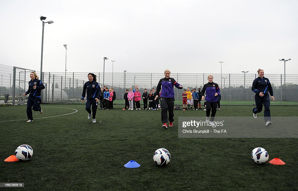 Kim Little and Steph Houghton of Arsenal Ladies FC and Siobhan Chambelain, Corinne Yorston and Laura Del Rio of Bristol Academy take part in a training session with local school children at Keepmoat Stadium on May 8, 2013 in Doncaster, England.