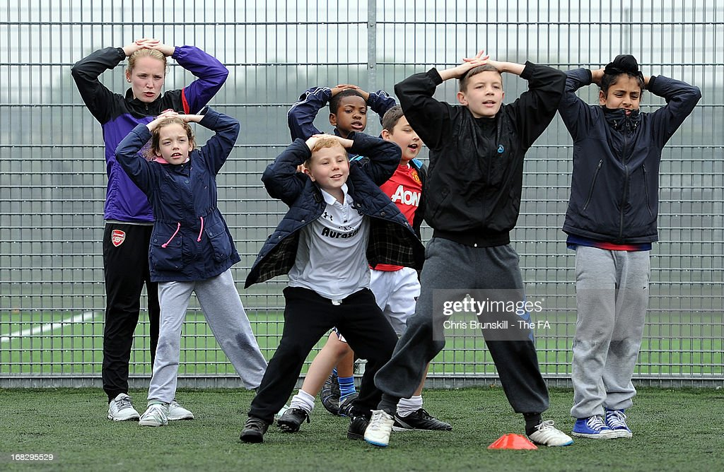 Kim Little (L) of Arsenal Ladies FC takes part in a training session with local school children at Keepmoat Stadium on May 8, 2013 in Doncaster, England.