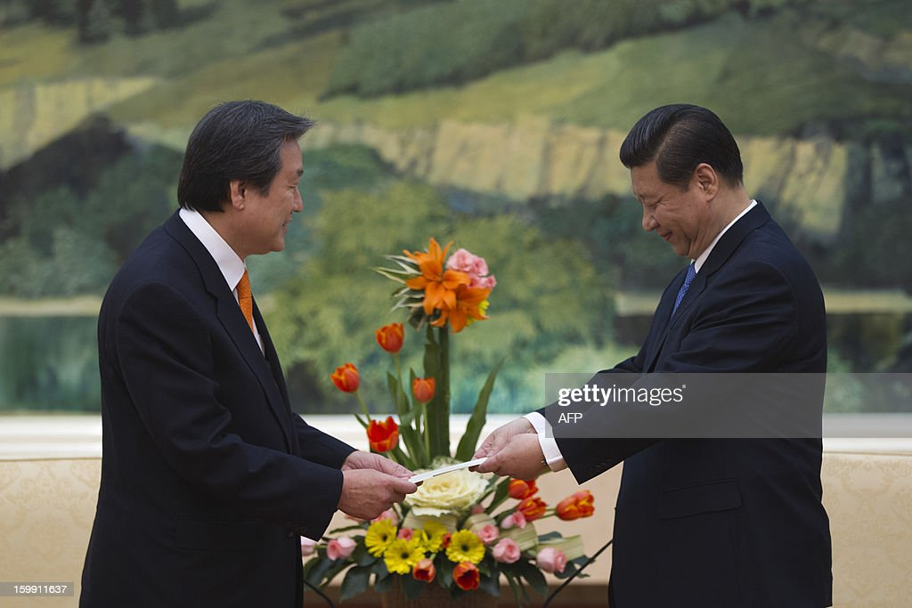 Kim Moo-sung (L), special envoy sent by South Korean President-elect Park Geun-hye, hands over a letter from Park to Chinese Vice President Xi Jinping during their meeting at the Great Hall of the People in Beijing on January 23, 2013.