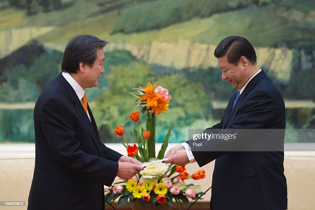 Kim Moo-sung, (L) special envoy sent by South Korean President-elect Park Geun-hye, hands over a letter from Park to Chinese Vice President Xi Jinping (R) during their meeting at the Great Hall of the People on January 23, 2013 in Beijing, China.