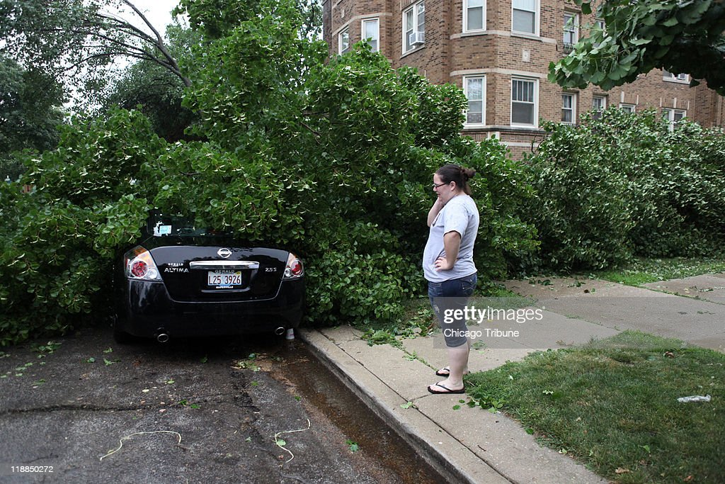 Kim Noble inspects the damage to her Nissan Altima after a storm caused damage and disrupted electricity in the area Monday July 11 2011 in Oak Park...