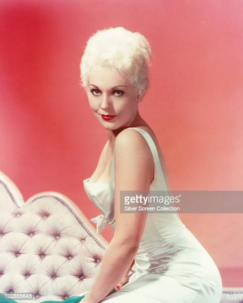 Kim Novak US actress wearing a white sleeveless dress posing on a bed in a studio portrait against a red background circa 1955