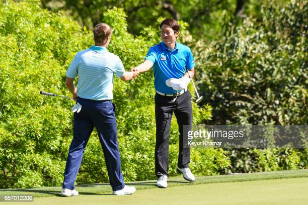 T Kim of Korea shakes hands with Russell Knox of Scotland after his 31 victory on the 17th hole green during round two of the World Golf...