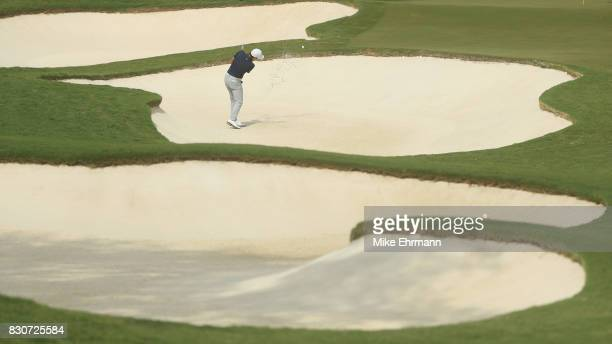 T Kim of South Korea plays a shot from a bunker on the first hole during the third round of the 2017 PGA Championship at Quail Hollow Club on August...