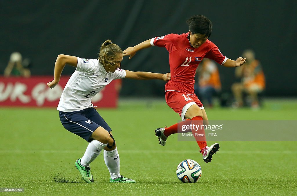 Kim Phyong Hwa (R) of Korea DPR and Eve Perisset (R) of France battle for the ball during the FIFA U-20 Women's World Cup 2014 3rd place playoff match between Korea DPR and France at Olympic Stadium on August 24, 2014 in Montreal, Canada.