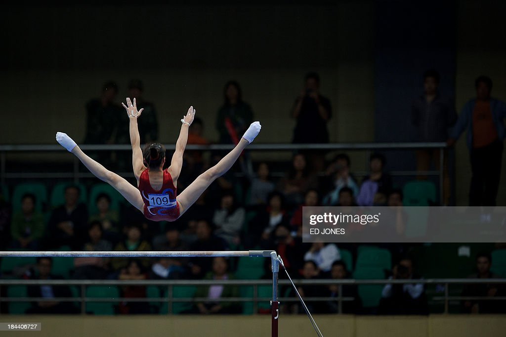Kim Pom of North Korea competes during the Women's Uneven Bars final gymnastics event of the 6th East Asian Games in Tianjin on October 13, 2013. The eastern Chinese city is hosting the East Asian Games which sees nine countries participating in 262 events across 22 different sports. AFP PHOTO / Ed Jones