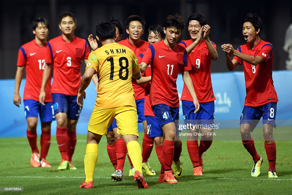 Kim Seungha#18 of Korea Republic celebrates with team-mates after saving the penalty to beat Iceland in the penalty shoot out after full time 1-1 draw during the 2014 FIFA Boys Summer Youth Olympic Football Tournament Semi Final match between Korea Republic and Iceland at Jiangning Sports Centre Stadium on August 24, 2014 in Nanjing, China.