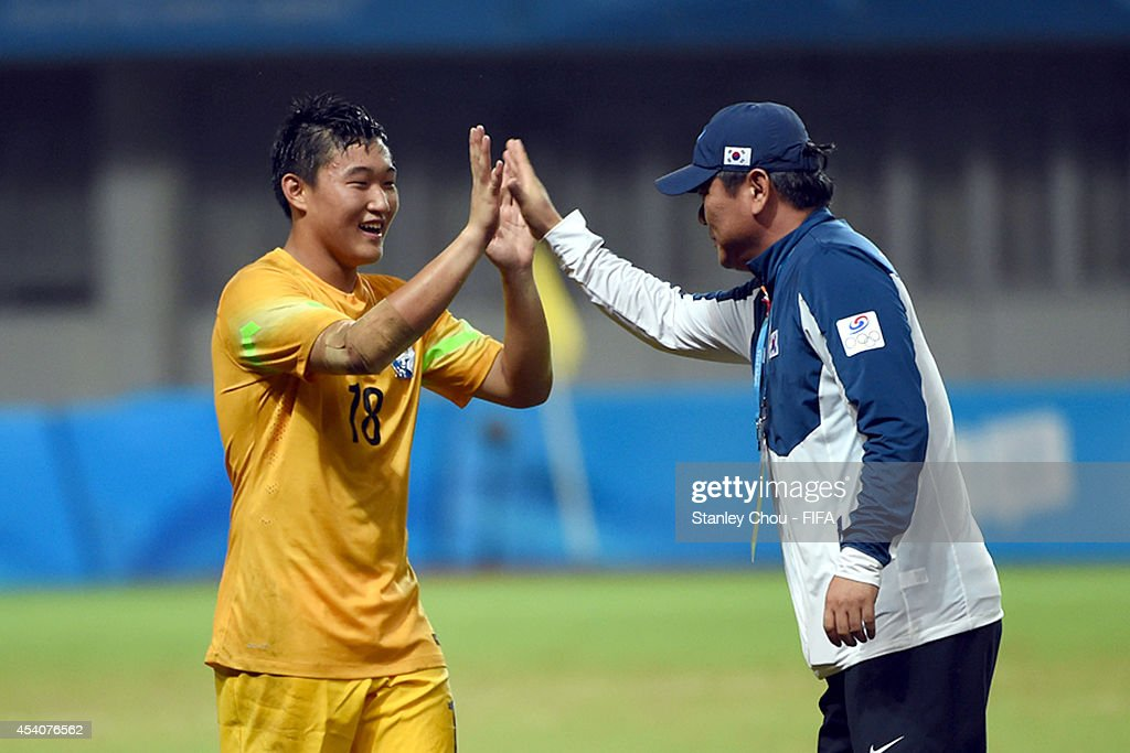 Kim Seungha#18 of Korea Republic is congratulated by his team official after saving the penalty to beat Iceland in the penalty shoot out after full time 1-1 draw during the 2014 FIFA Boys Summer Youth Olympic Football Tournament Semi Final match between Korea Republic and Iceland at Jiangning Sports Centre Stadium on August 24, 2014 in Nanjing, China.