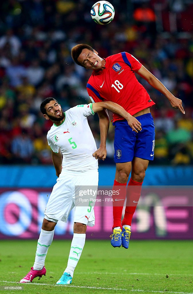 Kim Shin-Wook of South Korea and Rafik Halliche of Algeria compete for the ball during the 2014 FIFA World Cup Brazil Group H match between Korea Republic and Algeria at Estadio Beira-Rio on June 22, 2014 in Porto Alegre, Brazil.