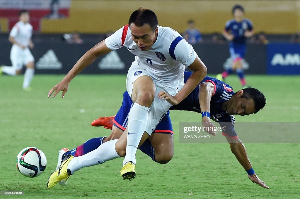 Kim Shinwook (L) of South Korea fights for the ball with Tomoaki Makino of Japan during men's East Asian Cup football match at the Wuhan Sports Center Stadium in Wuhan on August 5, 2015. AFP PHOTO / WANG ZHAO