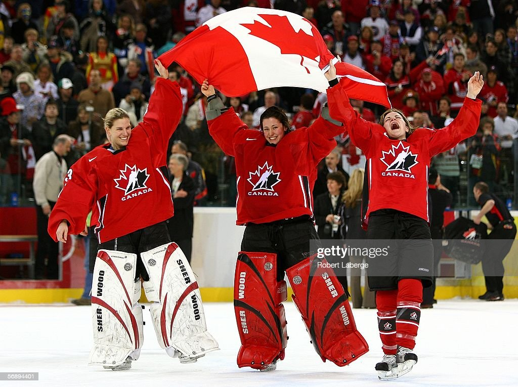 Kim St-Pierre #33, Charline Labonte #32 and Sarah Vaillancourt #26 of Canada celebrate after their 4-1 victory over Sweden during the final of the women's ice hockey on Day 10 of the Turin 2006 Winter Olympic Games on February 20, 2006 at the Palasport Olimpico in Turin, Italy.