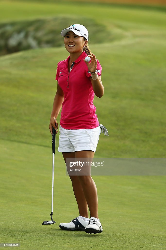 I.K. Kim waves to the crowd after finishing her round on the eighteenth green during the third round of the 2013 U.S. Women's Open at Sebonack Golf Club on June 29, 2013 in Southampton, New York.