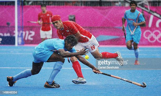 Kim Young Jin of South Korea and Tirkey Ignace challenge for the ball during the Men's Hockey match between India and South Korea on Day 9 of the...