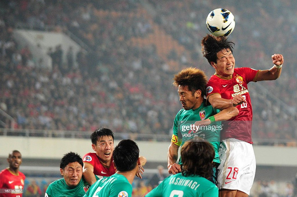 Kim Young-Gwon (R) of Guangzhou Evergrande jumps to head the ball during the AFC Champions League match between Guangzhou Evergrande and Urawa Red Diamonds at Tianhe Sports Center on February 26, 2013 in Guangzhou, China.