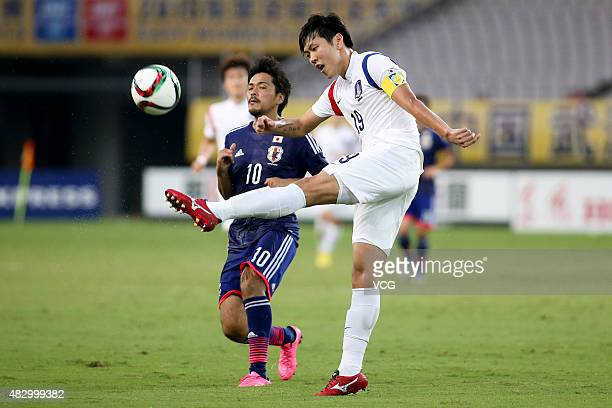Kim Younggwon of South Korea and Shinzo Koroki of Japan vie for the ball in group match between Japan and South Korea during EAFF East Asian Cup 2015...