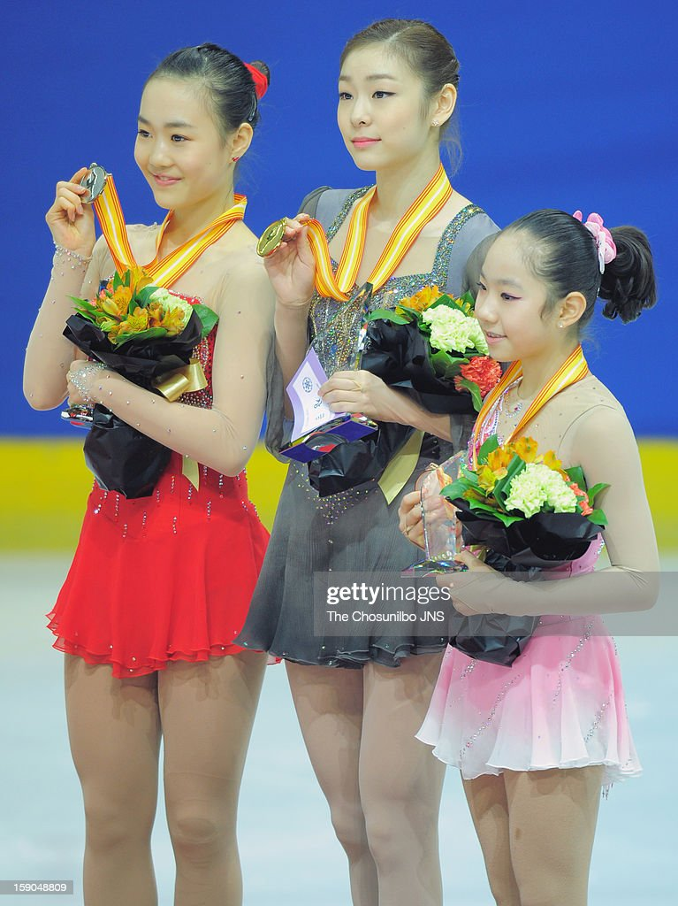 Kim Yu-Na (c) poses for photographs at the medal ceremony after the competition during day three of Korea Figure Skating Championshpis 2013 at Mokdong Ice Rink on January 6, 2013 in Seoul, South Korea.