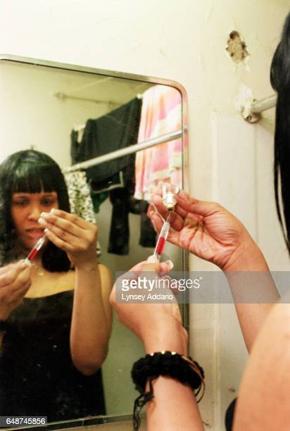 Kima prepares a shot containing Delestrogen and Vitamin B12 for her roommate Charisse in her bathroom in Harlem New York City on Dec 1 1999 Kima and...