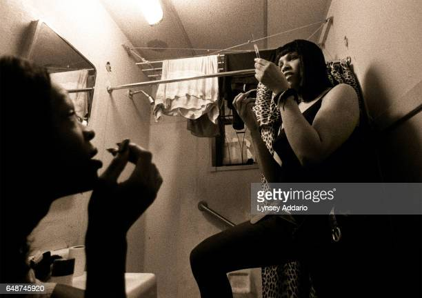 Kima right prepares a shot containing Delestrogen and Vitamin B12 for Charisse left in Kima's bathroom in Harlem New York City on Dec 1 1999 Kima and...