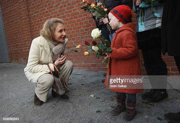 Kimberly Emerson wife of United States Ambassador to Germany John Emerson accepts a flower from Hulda at the Berlin Wall Memorial at Bernauer Strasse...